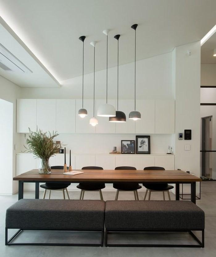 Tủ bếp tối giản màu trắng và chiếc bàn ăn bằng gỗ màu sẫm cùng với băng ghế tạo ra một không gian vô cùng lãng mạn