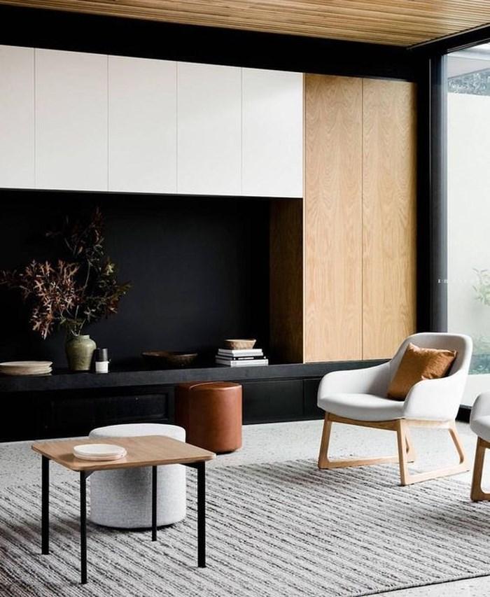 Một phòng khách đầy sự đối lập với ghế trắng, tường đen và đồ gỗ nhạt màu