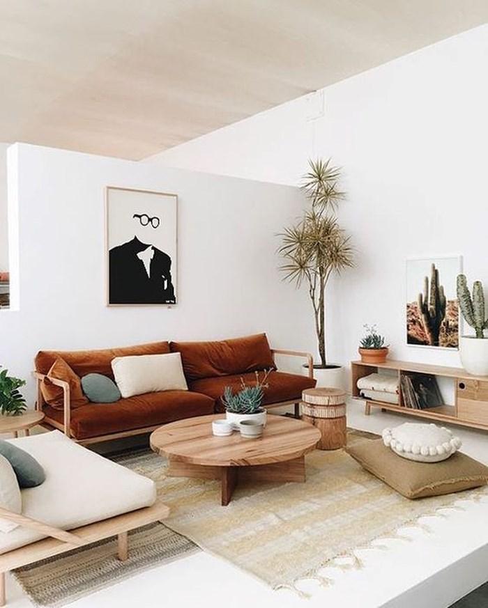 Phòng khách lãng mạn mà không kém phần cá tính với tường màu trắng, đồ gỗ nhạt màu và chiếc ghế bành màu rượu cognac cùng màu xanh của cây cối