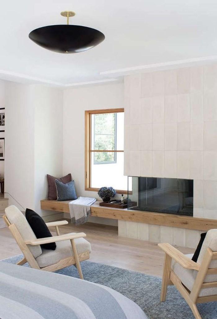 Những chiếc ghế thấp bằng gỗ nhạt màu kết hợp với đệm màu xám và các điểm nhấn màu đen bắt mắt. Đường cong và đường thẳng cũng được kết hợp thú vị